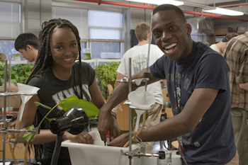 A male and female smile for the camera as they work on their plant project during a BIOL 1108 lab