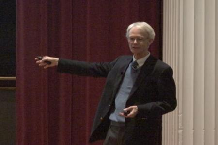 Claiborne Glover gestures as he delivers his lecture on the Origins of Biomolecules on the stage of the UGA Chapel